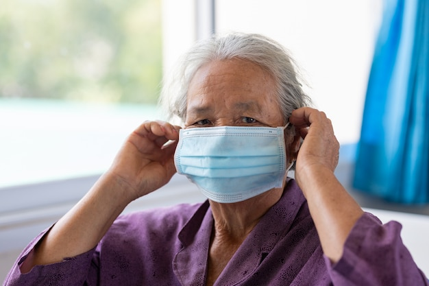 Hogere aziatische vrouw die gezichtsmasker draagt tijdens coronavirus en griepuitbraak. ziekte- en ziektebescherming. de verouderende vrouwelijke patiënt die risico loopt op infectie corona virus [covid-19].