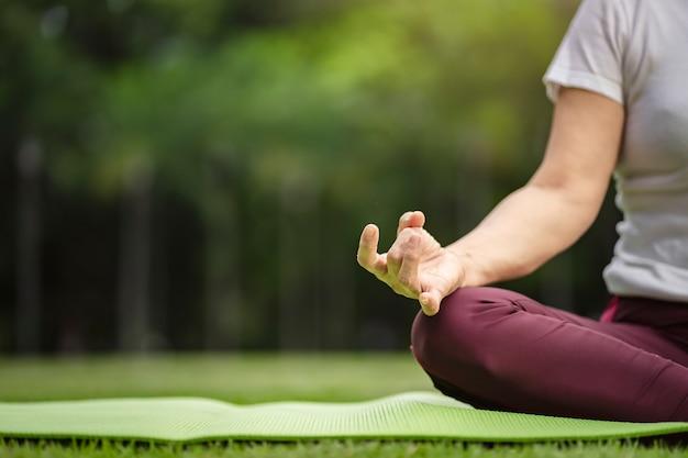 Hogere aziatische vrouw het praktizeren yogaoefening openlucht in de ochtend. senior gezonde levensstijl