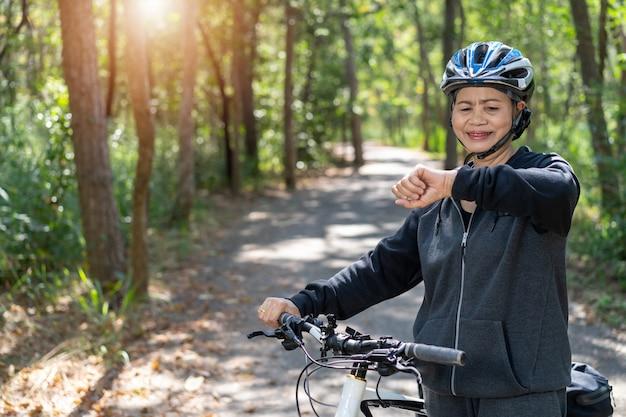 Hogere aziatische vrouw in fiets in het park
