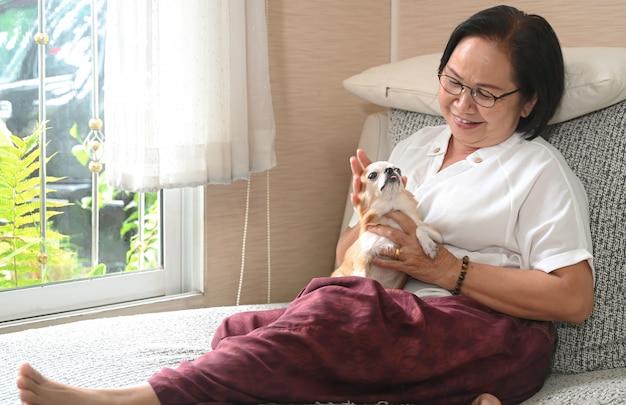 Hogere aziatische vrouwenzitting met een hond op de bank, rustte zij en glimlachte.