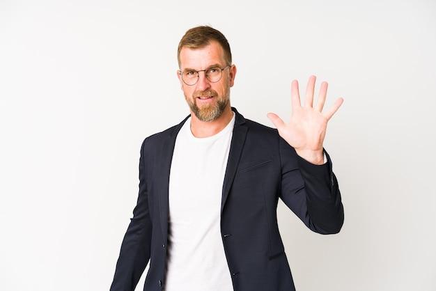 Hogere bedrijfsmens die op witte muur wordt geïsoleerd die vrolijk toont nummer vijf met vingers.