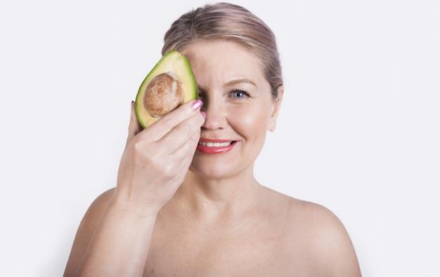 Hogere blonde vrouw met naakte schouders die haar gezicht bedekken met een avocadoglimlach bij camera