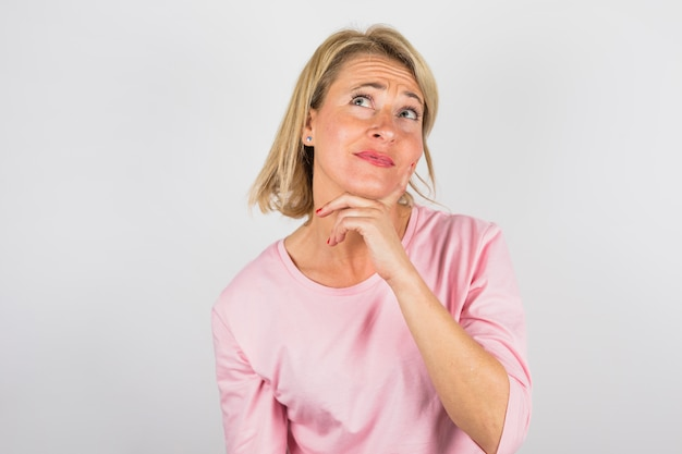 Hogere charmante peinzende vrouw in roze blouse