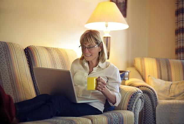 Hogere dame die laptop met behulp van