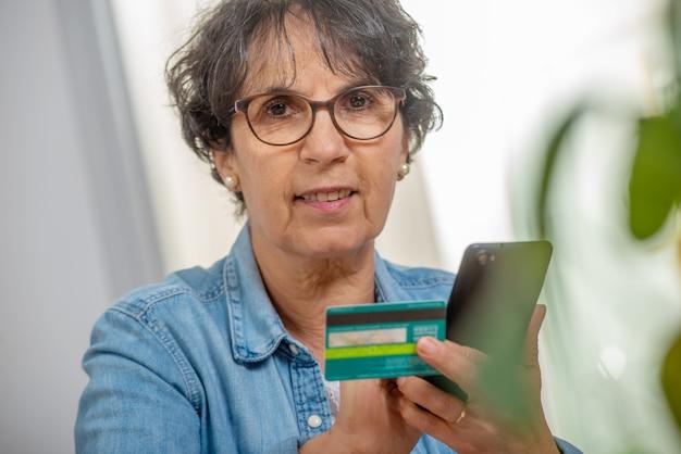 Hogere donkerbruine vrouw die met internet winkelt