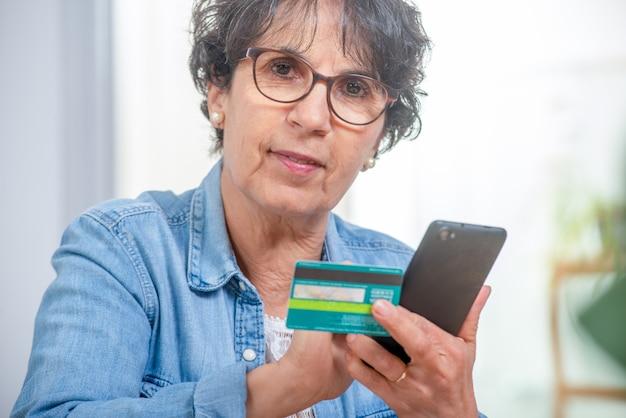 Hogere donkerbruine vrouw die met smartphone en internet winkelt