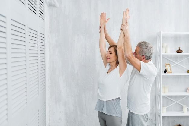 Hogere echtgenoot die zijn vrouw helpt die yogapositie doet