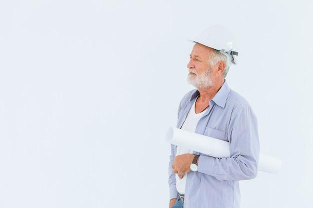 Hogere ernstige bouwingenieur met bouwvakker met document broodjesblauwdruk in studio met witte ruimte voor tekst
