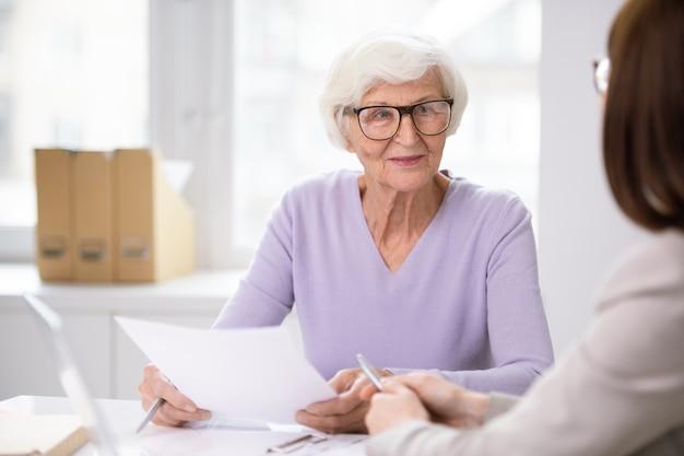 Hogere glimlachende vrouwelijke cliënt die met verzekeringsformulier naar haar agent luistert die voorwaarden van overeenkomst uitlegt