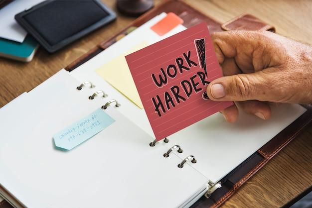 Hogere hand die de harde kleverige nota van het werk houdt