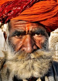 Hogere indische mens die de camera bekijkt.