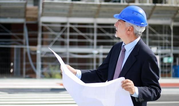 Hogere ingenieur die een blauwdruk i voorzijde van een bouwwerf leest