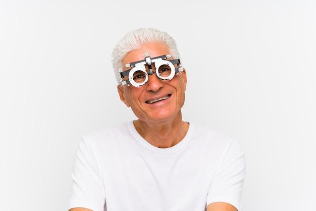 Hogere kaukasische mens die een optometrist proefframe gelukkig, glimlachend en vrolijk draagt.