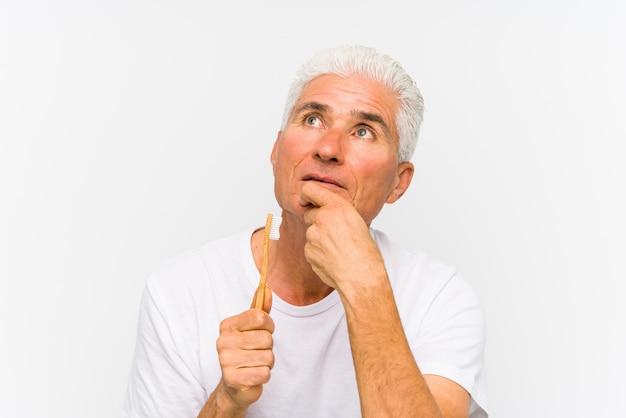 Hogere kaukasische mens die een tandenborstel geïsoleerd houden zijdelings het kijken met twijfelachtige en sceptische uitdrukking houden.