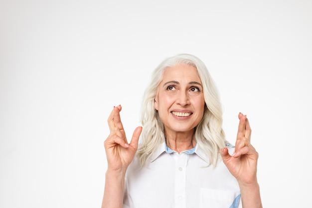Hogere kaukasische vrouw die over iets aangenaam denkt en wens met gekruiste vingers maakt, die over witte muur wordt geïsoleerd