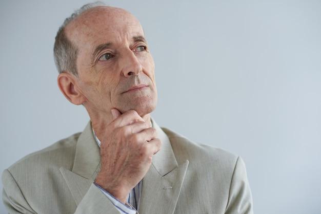 Hogere kaukasische zakenman wat betreft kin en weg kijkend met dromerig gezicht