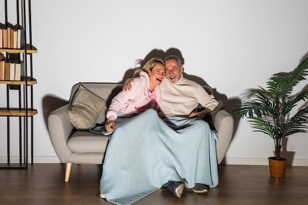 Hogere lachende man die vrouw koestert en op tv op sofa let