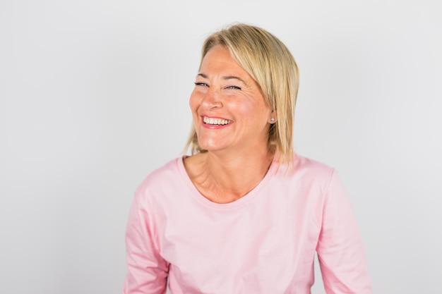 Hogere lachende vrouw in roze blouse
