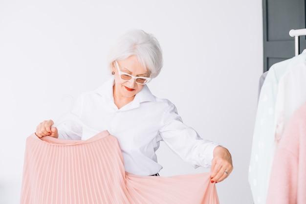 Hogere levensstijl. mode kleding winkelen. zelfverzekerde oudere dame die een elegant kledingstuk probeert.