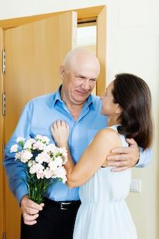 Hogere man die bos van bloemen geeft aan vrouw