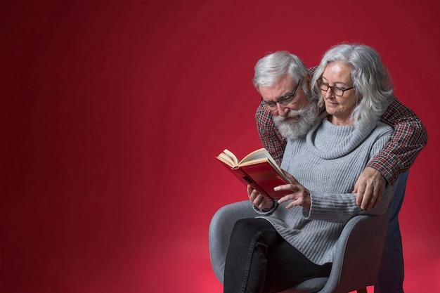 Hogere man die haar vrouw omhelst die het boek leest tegen rode achtergrond