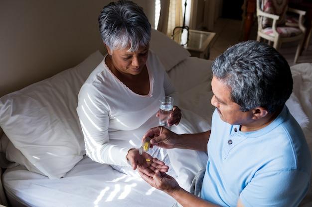 Hogere man die hogere vrouw geeft aan geneeskunde in slaapkamer