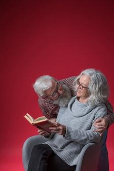 Hogere man die van haar vrouwenzitting op stoel houden die het boek lezen tegen rode achtergrond