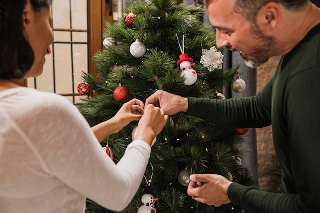 Hogere man die zijn vrouw met decoratie helpt