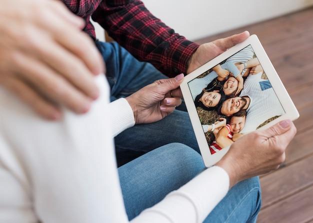 Hogere man en vrouw die door beelden op hun tablet kijken