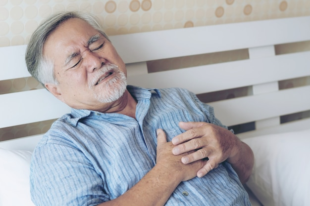 Hogere mannelijke aziaat die aan slechte pijn in zijn hartaanval van de borst thuis lijden - hogere hartkwaal