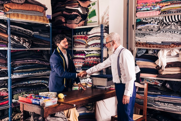 Hogere mannelijke klant het schudden handen met jonge mannelijke kleermaker in zijn workshop