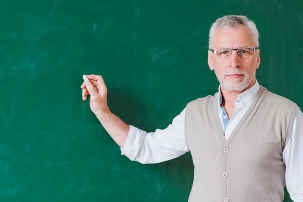 Hogere mannelijke leraar die op groen bord schrijft