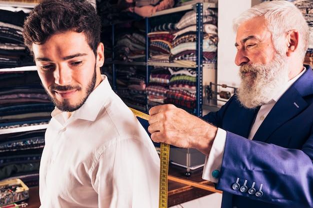 Hogere mannelijke manierontwerper die meting van zijn klant in de winkel neemt
