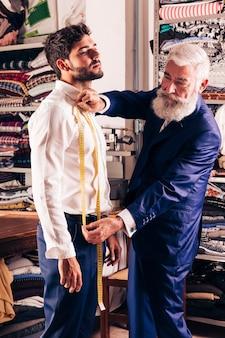 Hogere mannelijke manierontwerper die metingen van de mens in zijn winkel nemen