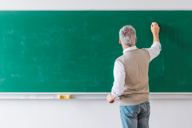 Hogere mannelijke professor die op bord met krijt schrijft