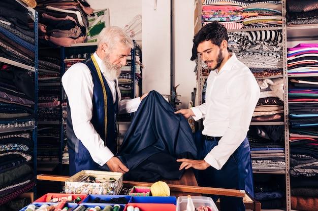 Hogere mannelijke verkoper die stoffen aanbieden aan de jonge mens in textielwinkel