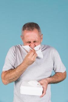 Hogere mens besmet met koude en griep die zijn neus in papieren zakdoekje blazen