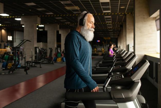 Hogere mens bij het runnen van machine in gymnastiek