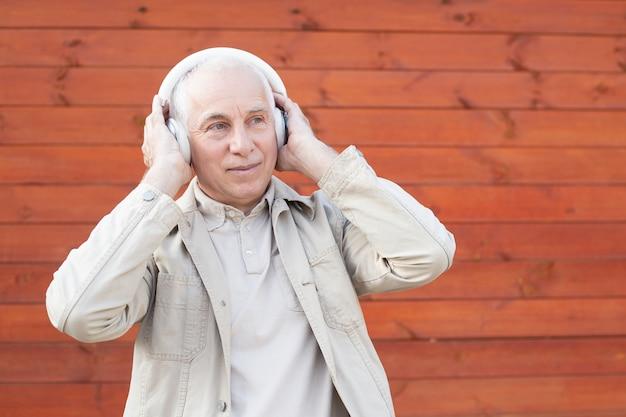 Hogere mens die aan muziek op hoofdtelefoon luistert, gelukkige succesvolle hogere zakenman.
