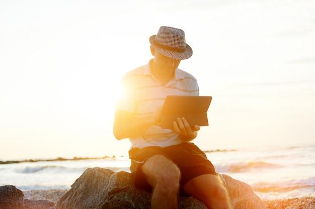 Hogere mens die aan zijn laptop op het strand tijdens zonsondergang werkt