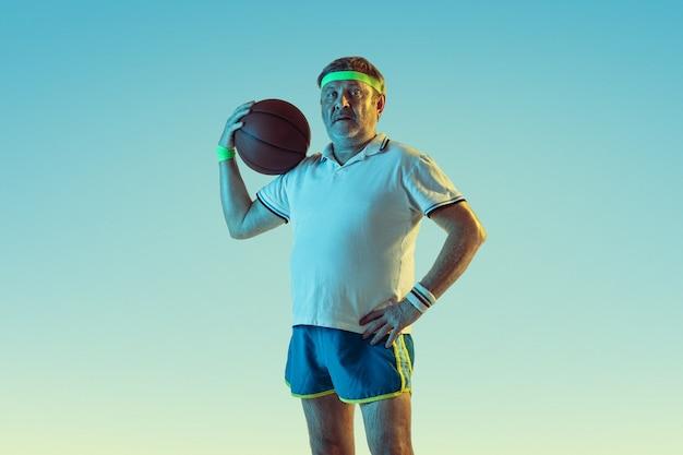 Hogere mens die basketbal op gradiëntmuur speelt in neonlicht