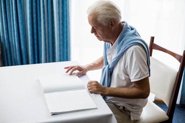 Hogere mens die braille gebruikt om te lezen