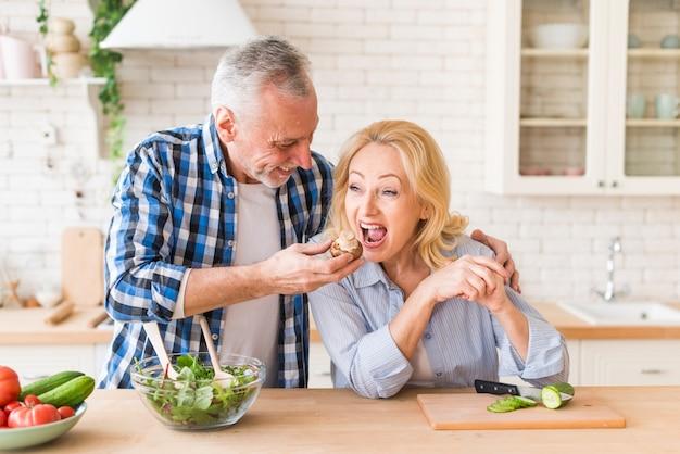 Hogere mens die de paddestoel voedt aan haar vrouw in de keuken
