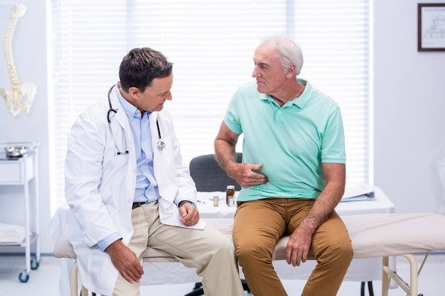 Hogere mens die de pijn van de maagpijn tonen aan arts