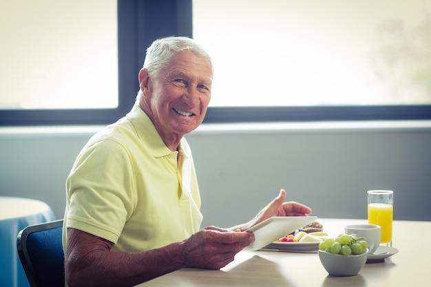 Hogere mens die digitale tablet gebruikt terwijl het hebben van ontbijt