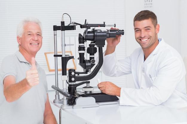 Hogere mens die duimen toont omhoog terwijl het zitten met opticien