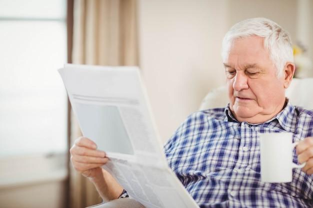 Hogere mens die een kop van koffie heeft en krant in woonkamer leest