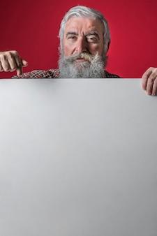 Hogere mens die haar vinger naar beneden op leeg wit aanplakbiljet tegen rode achtergrond richt