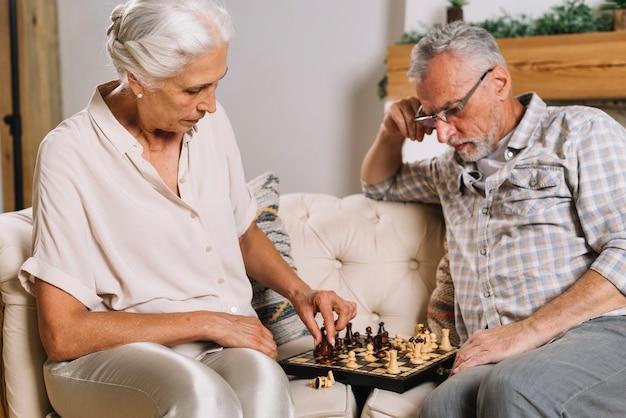 Hogere mens die haar vrouw het spelen schaak bekijkt