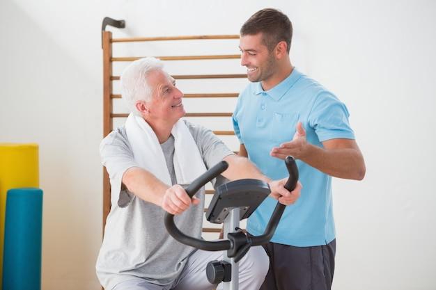 Hogere mens die hometrainer met zijn trainer doet